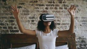 Donna afroamericana riccia che ottiene esperienza facendo uso dei vetri della cuffia avricolare di VR 360 di realtà virtuale a ca Immagine Stock