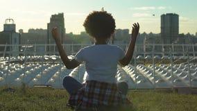 Donna afroamericana rilassata che si siede nella posa del loto, meditante al tramonto, resto archivi video