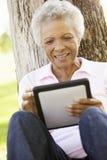 Donna afroamericana senior in parco facendo uso del computer della compressa Fotografia Stock