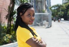 Donna afroamericana sorridente in camicia gialla che guarda lateralmente Immagini Stock