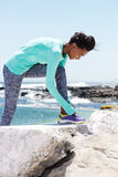 Donna afroamericana sorridente che lega i laccetti prima dell'allenamento Fotografie Stock