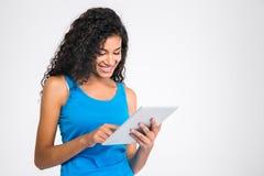 Donna afroamericana sorridente che per mezzo del computer della compressa Immagini Stock Libere da Diritti