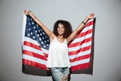Donna afroamericana sorridente che tiene la bandiera di U.S.A. Immagine Stock