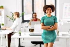 Donna afroamericana sorridente felice all'ufficio Immagine Stock
