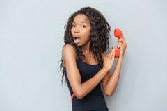 Donna afroamericana stupita che tiene il retro tubo del telefono Immagini Stock Libere da Diritti