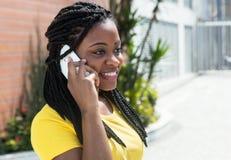 Donna afroamericana sveglia in una camicia gialla che ascolta al telefono cellulare Fotografia Stock