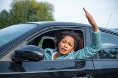 Donna aggressiva che conduce automobile che grida a qualcuno immagini stock