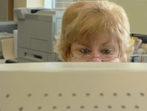 Donna aggrottante le sopracciglia che esamina calcolatore Immagini Stock Libere da Diritti