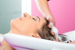 Donna ai capelli di lavaggio del parrucchiere Immagini Stock