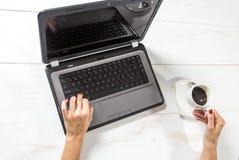 Donna al computer portatile con la tazza di caffè immagine stock libera da diritti