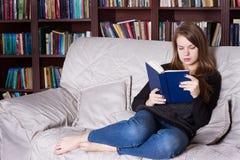 Donna al libro di lettura delle biblioteche Immagini Stock