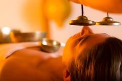 Donna al massaggio di Wellness con le ciotole di canto fotografie stock