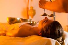 Donna al massaggio di Wellness con le ciotole di canto Immagini Stock