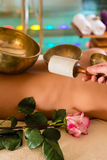 Donna al massaggio di Wellness con le ciotole di canto fotografia stock