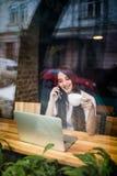 Donna al self-service facendo uso del telefono e del computer portatile e della tazza di caffè della bevanda Fotografie Stock Libere da Diritti