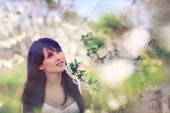 Donna in alberi di fioritura in primavera Fotografia Stock