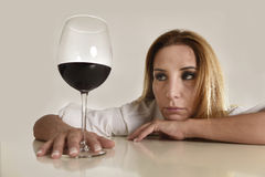 Donna alcolica depressa sprecata bionda caucasica che beve dipendenza di alcool di vetro del vino rosso Immagini Stock