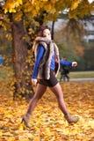 Donna all'autunno che cammina sui fogli gialli Immagini Stock Libere da Diritti