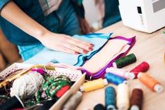 Donna alla fabbrica dell'indumento Sta scegliendo il materiale ed il colore per il vestito immagini stock