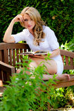 Donna alla lettura del libro nel giardino Fotografia Stock Libera da Diritti