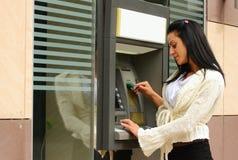 Donna alla macchina di bancomat Immagini Stock