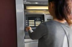 Donna alla macchina di bancomat con l'icona del bitcoin sullo schermo fotografia stock