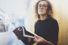 Donna alla moda affascinante con i vetri degli occhi che legge seduta della rivista dell'interno in caffè urbano Ritratto casuale Fotografie Stock