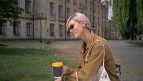 Donna alla moda bionda in occhiali da sole con il caffè bevente dei capelli di scarsità ed esaminare macchina fotografica, sorrid archivi video