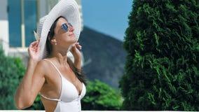Donna alla moda in cappello ed occhiali da sole che gode del prendere il sole e del sorridere al parco dell'hotel di estate video d archivio