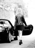 Donna alla moda che cammina all'automobile fotografia stock libera da diritti