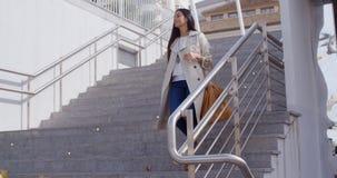 Donna alla moda che cammina giù un volo delle scale Immagine Stock
