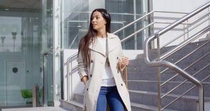 Donna alla moda che cammina giù un volo delle scale Immagini Stock