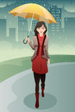 Donna alla moda che cammina nella pioggia che porta un ombrello Fotografia Stock Libera da Diritti
