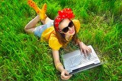 Donna alla moda che per mezzo dei computer portatili Immagini Stock Libere da Diritti