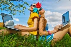 Donna alla moda che per mezzo dei computer portatili Fotografie Stock Libere da Diritti
