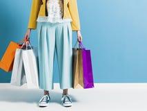 Donna alla moda che porta molti sacchetti della spesa fotografia stock libera da diritti