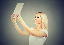 Donna alla moda che prende selfie con la compressa immagini stock