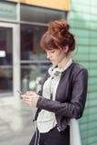 Donna alla moda che scrive sul suo telefono alle inferriate Fotografia Stock Libera da Diritti