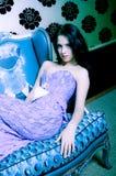 Donna alla moda che si distende sul sofà fotografia stock libera da diritti