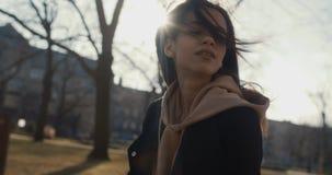 Donna alla moda che si rilassa in un parco della città durante il giorno soleggiato Immagine Stock