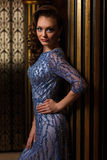 Donna alla moda che sta la colonna vicina dell'oro Fotografia Stock
