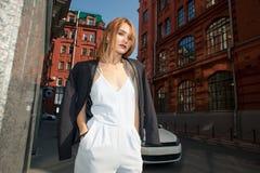 Donna alla moda che sta sul marciapiede e che esamina il dist fotografie stock