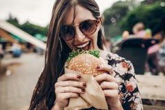 donna alla moda dei pantaloni a vita bassa che mangia hamburger succoso chee mordace della ragazza di boho immagine stock libera da diritti