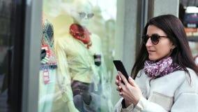Donna alla moda del cliente che prende foto del manichino in vetrina dei vestiti di modo del negozio facendo uso dello smartphone video d archivio