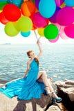 Donna alla moda di modo di lusso con i palloni a disposizione sulla spiaggia Fotografia Stock