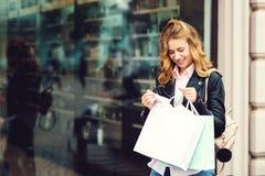 Donna alla moda felice con i sacchetti della spesa che stanno alla finestra del negozio Concetto di stile di vita Emozioni positi immagine stock libera da diritti