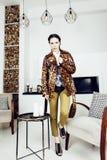 Donna alla moda graziosa in vestito da modo con la stampa del leopardo nell'interno di lusso della casa, concetto della gente di  immagini stock