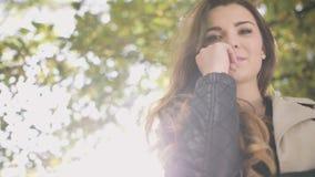 Donna alla moda premurosa che sorride nel parco di autunno archivi video