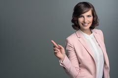 Donna alla moda sorridente che indica lo spazio della copia Immagini Stock