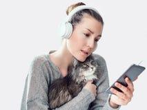 Donna alla moda, telefono cellulare e gattino delicato fotografia stock